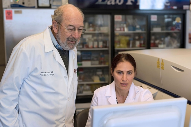 Man and woman in lab coats look at a computer screen